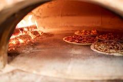 Pizza baking in oven at pizzeria. Food, italian kitchen and cooking concept - pizza baking in oven at pizzeria stock photos