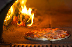 Pizza baking in traditional stone oven Stock Images