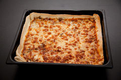 Pizza in a baking tray Stock Photo