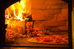 Pizza baking in wood fired oven. Thin crust pizza baking in wood fired oven Royalty Free Stock Image