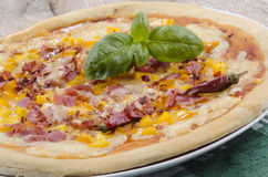 Pizza with ham and yellow paprika Stock Images