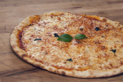 Pizza with basil on wooden table. Margherita pizza with basil leaves and rucola on a wooden table Stock Photo