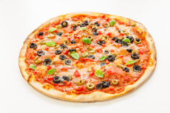 Pizza. Beautiful multi colored and crispy pizza with basil, melted cheese and salami slowly turning on rotating table with white background Stock Photo