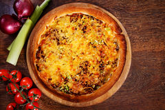 Pizza with beef stuffing, leek and cheese served on wooden table Royalty Free Stock Images