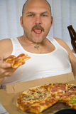 Pizza and beer. Man sitting on the couch with a pizza and a bottle of beer Royalty Free Stock Photography