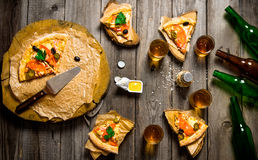 Pizza and beer for four people. On a wooden table. Stock Photo