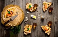 Pizza and beer for four people. On a wooden table. Royalty Free Stock Photography