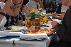Pizza and a beer - late lunch with friends. Stock Photos