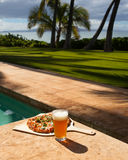 Pizza and beer by the poolside in Hawaii. Poolside dining in Maui, Hawaii stock photo