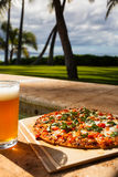 Pizza and beer by the poolside in Hawaii. At dusk Royalty Free Stock Photos