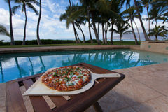 Pizza and beer by the poolside in Hawaii Royalty Free Stock Photos