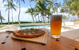 Pizza and beer by the poolside in Hawaii Royalty Free Stock Image