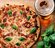 Pizza and beer on wooden table royalty free stock photography