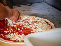 Pizza being assembled Royalty Free Stock Image