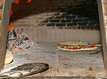 Pizza being baked in a wood fire brick oven in a restaurant Royalty Free Stock Images