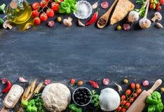 Pizza-Bestandteile auf schwarzer Tabelle in einem rohen stockbild