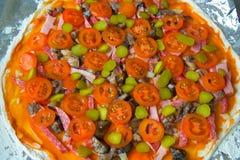 Pizza, bevor sie backt, ist auf dem Tisch Lizenzfreie Stockbilder