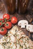Pizza, bière, champignons de paris et tomates-cerises sur un fond en bois Photographie stock
