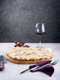 Pizza bianca with chicken, ham and cream sauce on wooden board next to a glass of wine, grapes and pieces of cheese Stock Photo