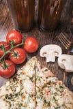 Pizza, Bier, Champignons und Kirschtomaten auf einem hölzernen Hintergrund Stockfotografie