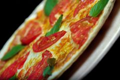 Pizza on black background. Delicious pizza with tomato and herbs Royalty Free Stock Photography