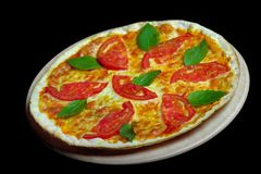 Pizza on black background. Delicious pizza with tomato and herbs Stock Image