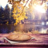 Pizza boapd and napkin on table over blurred trees and river as background, product display template stock photography