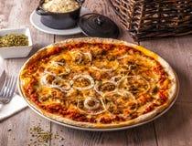Pizza Bolognese tjänade som med lökar, oreganon och ost på en rost Fotografering för Bildbyråer