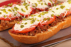 Pizza Bread. Closeup of a loaf of french bread with hamburger tomatoes and cheese on top Stock Photography