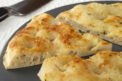 Pizza Bread with Slice Cut. Pizza bread with garlic and herbs, on a platter with one slice cut stock photography