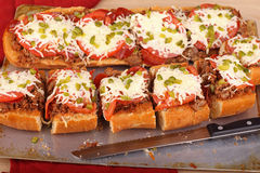 Pizza Bread. Loaf of french bread with hamburger tomatoes and cheese on top Stock Image