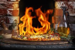 Pizza Brick Fire Oven. A hot sausage and vegetable pizza on pizza stone with glass decanter of olive oil and fire from brick oven in background royalty free stock images