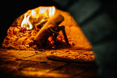 Pizza and brick pizza oven with fire. Pizza and brick pizza oven Royalty Free Stock Images