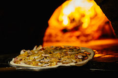 Pizza and brick pizza oven with fire. Pizza and brick pizza oven Royalty Free Stock Image