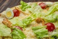 Pizza Caesar z kurczakiem i pomidorami na drewnianym tle zdjęcie royalty free