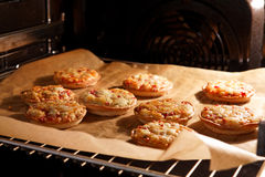 Pizza cakes. Delicious little Italian pizza cakes in a hot oven Royalty Free Stock Photo