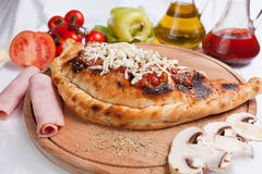 Pizza Cal-zone. With ham, mushroom and tomatoes and oil royalty free stock images