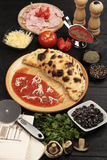 Pizza Calzone. Studio shot of pizza Calzone and ingredients Royalty Free Stock Images