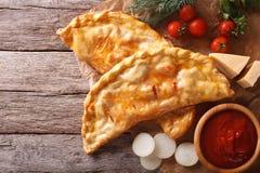 Pizza calzone auf einem Papier und Bestandteilen horizontale Draufsicht Stockfotos