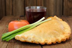 Pizza calzone with glass of red wine, fresh scallion and tomato Royalty Free Stock Photography