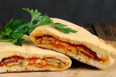 Pizza calzone with mushrooms and fresh parsley Royalty Free Stock Photos
