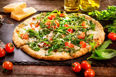 Pizza Caprese with arugula, cheese, yoghurt and cherry tomatoes. Closeup stock photography