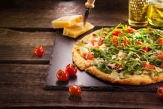 Pizza Caprese with arugula, cheese, yoghurt and cherry tomatoes stock image