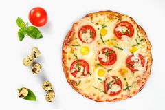 Pizza caprese top view on white background. Pizza caprese top view with quail eggs with tomato and basil leaves beside, on white background stock photos
