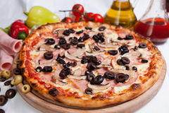 Pizza Capricciosa. With ham, mushrooms and black olive and tomatoes stock photos