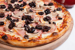 Pizza Capricciosa on a wood plate Stock Photography