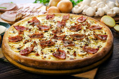 Pizza Carbonara with bacon 2. Pizza Carbonara with bacon and cheese on the table Royalty Free Stock Image