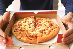 Pizza in cardboard box with kids hands. Close up photo stock photography