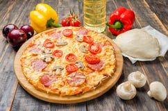 Pizza casalinga con i pomodori ed i funghi su una tavola di legno con le verdure immagini stock libere da diritti