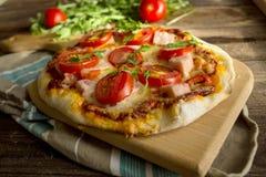 Pizza casalinga con il prosciutto, il pomodoro e la rucola Immagine Stock Libera da Diritti